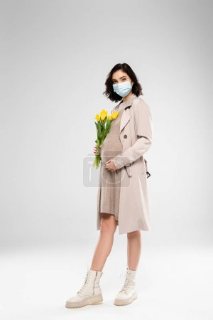 Pregnant woman in medical mask holding flowers on grey background