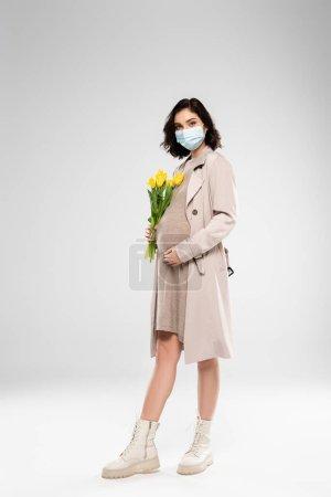 Femme enceinte en masque médical tenant des fleurs sur fond gris