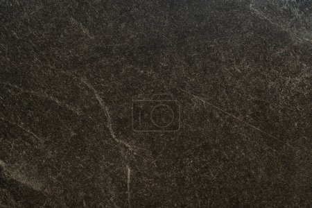 background of black marble surface with streaks, top view