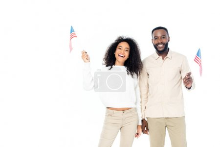 joyful african american couple smiling at camera while holding small flags of usa isolated on white