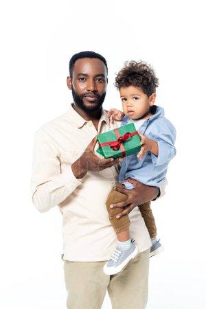 Photo pour Jeune homme afro-américain tenant enfant en bas âge fils et boîte cadeau isolé sur blanc - image libre de droit