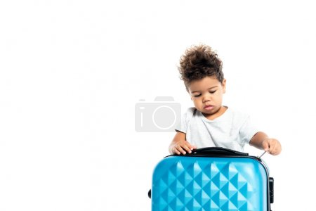 little african american boy opening suitcase isolated on white