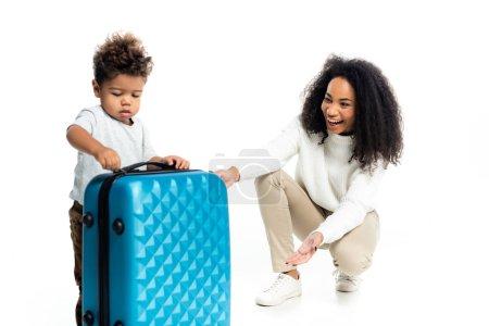 Photo pour Rire femme afro-américaine pointant vers sac de voyage près du petit fils sur blanc - image libre de droit
