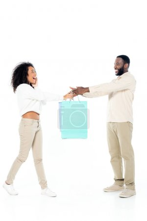 glücklich afrikanisch-amerikanischer Mann gibt erstaunten Ehefrau Einkaufstüten auf weiß