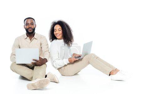 Afrikanisch-amerikanischer Mann blickt in die Kamera neben neugieriger Frau, die auf seinen Laptop auf weiß schaut