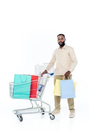 Photo pour Jeune homme afro-américain regardant la caméra tout en se tenant près du panier d'achat sur blanc - image libre de droit