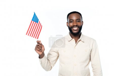 cheerful african american man smiling at camera while holding small flag of usa isolated on white