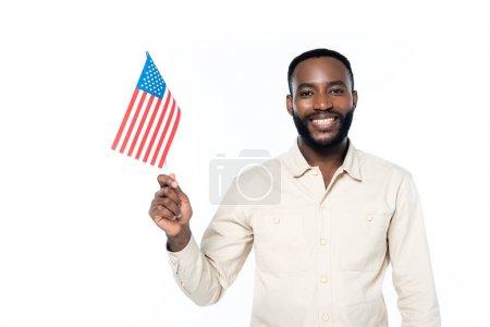 fröhlicher afrikanisch-amerikanischer Mann lächelt in die Kamera, während er eine kleine US-Fahne auf weißem Grund hält