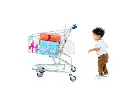 Photo pour Petit garçon afro-américain debout près du chariot avec des cadeaux sur blanc - image libre de droit