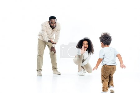 excited african american woman giving high five to toddler son walking on white