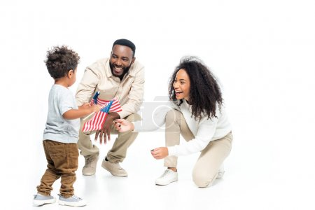 african american boy holding small flags of usa near laughing parents n white