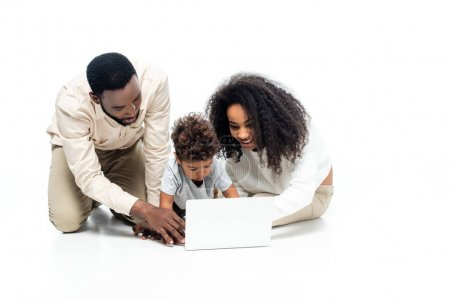 Photo for African american couple using laptop together with toddler son on white - Royalty Free Image