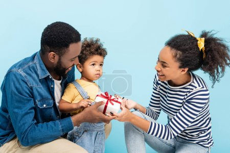 joyful african american parents presenting gift to son isolated on blue