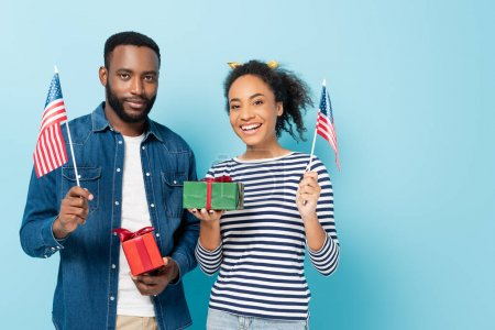 smiling african american couple holding gift boxes and small flags of usa on blue