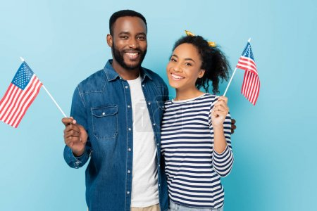 cheerful african american couple holding small flags of usa while looking at camera isolated on blue