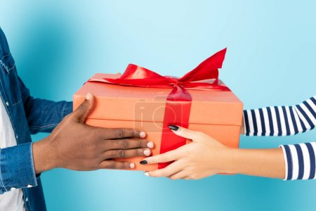cropped view of african american husband and wife holding gift box on blue