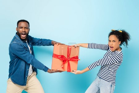 envy african american husband and wife taking away gift box from each other on blue