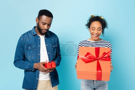 offended african american man holding small gift near astonished wife with big present on blue