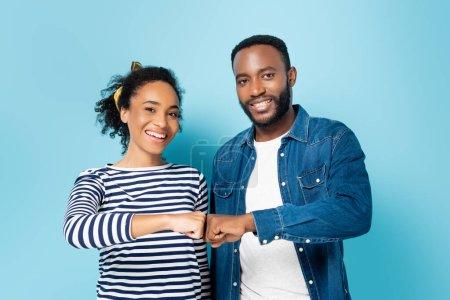 Photo pour Joyeux couple afro-américain faire poing bosse tout en regardant la caméra sur bleu - image libre de droit