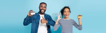 podekscytowani afrykańska para trzyma karty kredytowe i pokazuje jak i w porządku gesty na niebieskim, sztandar