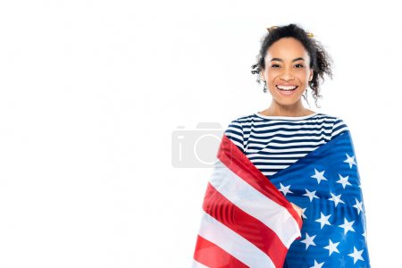 cheerful african american woman, wrapped in usa flag, smiling at camera isolated on white
