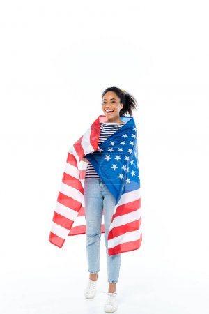 full length view of happy african american woman, wrapped in usa flag on white