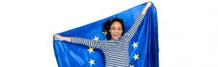 joyful african american woman holding flag of european union isolated on white, banner