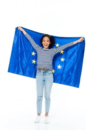 full length view of cheerful african american woman holding flag of european union on white