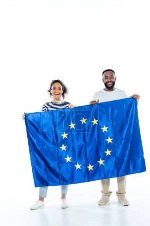 young african american couple smiling at camera while holding european union flag on white