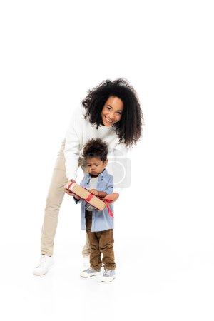 Photo pour Gai afro-américaine femme regardant caméra près de fils avec boîte cadeau sur blanc - image libre de droit