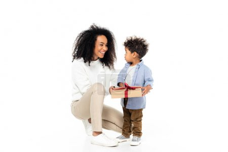 happy african american mother looking at toddler son holding present on white