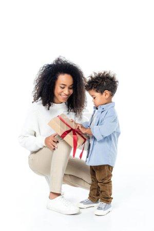 Photo pour Afro-américain enfant ouverture boîte cadeau près de mère souriante sur blanc - image libre de droit