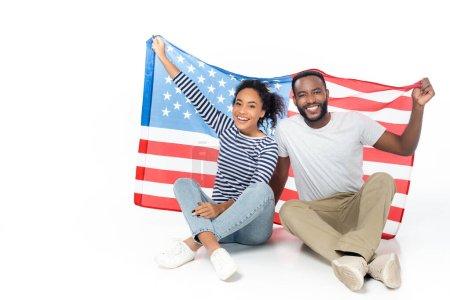 fröhliches afrikanisch-amerikanisches Paar blickt in die Kamera, während es mit einer US-Flagge auf weiß sitzt
