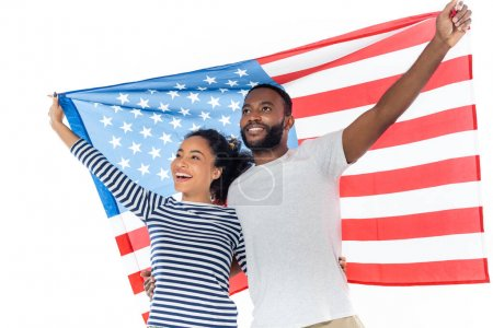 excited african american couple looking away while standing with usa flag isolated on white