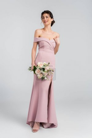 full length view of elegant fiancee looking away while holding wedding bouquet on grey