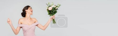 Photo for Excited fiancee showing win gesture while holding wedding bouquet isolated on grey, banner - Royalty Free Image