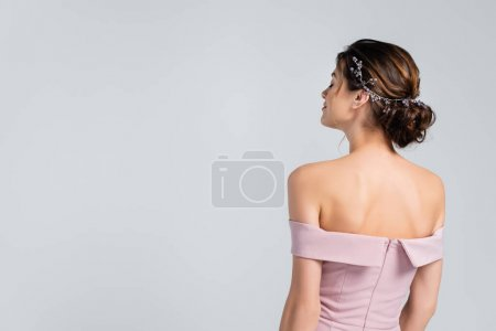 back view of bride in pink dress, with naked shoulders, posing isolated on grey