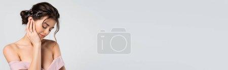 Charmante Braut mit geschlossenen Augen und anrührendem Gesicht isoliert auf grauem Banner stehend