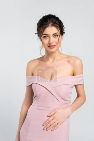 charming woman in elegant, pink dress looking at camera isolated on grey