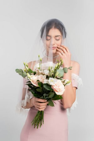 young bride in veil holding wedding bouquet while standing with closed eyes isolated on grey