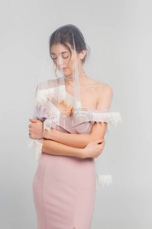 Photo for Sensual woman in elegant dress and veil standing with closed eyes isolated on grey - Royalty Free Image