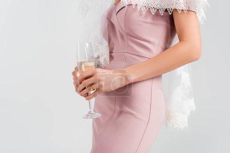 Teilansicht einer Frau in rosa Kleid und Schleier mit Champagner auf grau