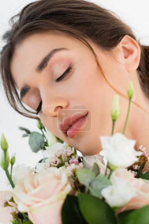 close up view of young woman with natural makeup near wedding bouquet isolated on white
