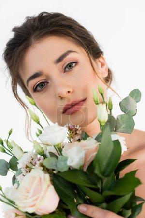sinnliche Frau mit natürlichem Make-up blickt in die Kamera in der Nähe von Brautstrauß isoliert auf weiß