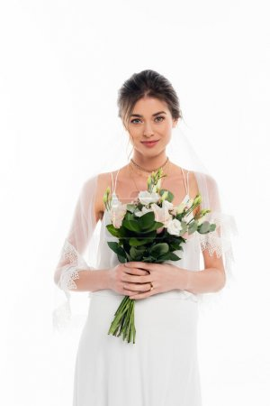 happy, pregnant bride looking at camera while holding wedding bouquet isolated on white