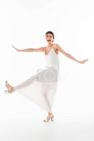 vista completa de la novia alegre mirando a la cámara mientras baila en blanco