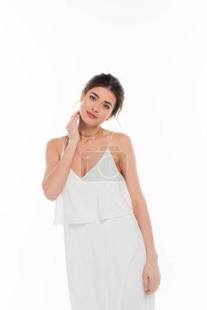 sinnliche Frau im Brautkleid, die den Hals berührt, während sie isoliert auf Weiß posiert