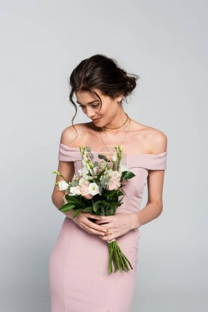 happy young bride in pink dress holding wedding bouquet isolated on grey