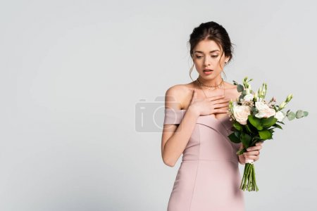 tense bride holding hand on chest while standing with wedding bouquet isolated on grey