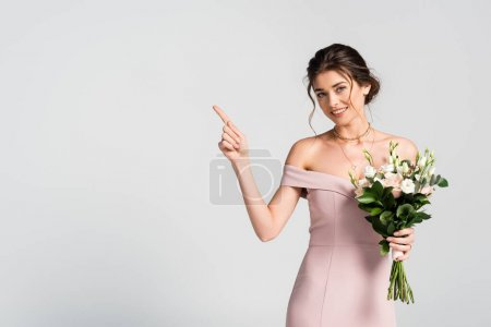 happy woman pointing with finger while holding wedding bouquet isolated on grey